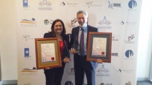 Business of the Year Award winners Lyn and Maurice Beinat holding two trophies and two plaques. Award Winners with Retrofit Solutions