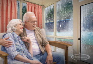 Old couple sitting comfortably in their living room while there is heavy snowing outside